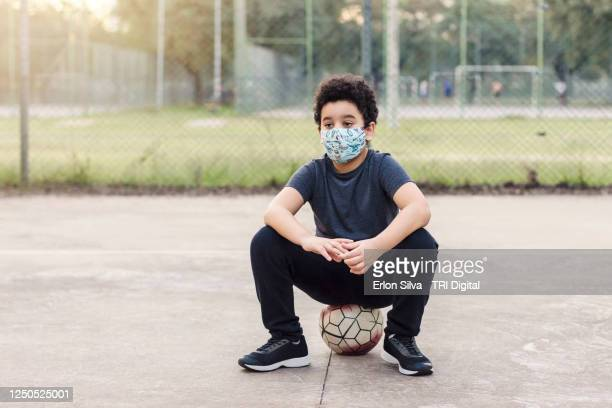 kid in social distance and wearing mask resting after playing football alone in the park - bronzage masque photos et images de collection