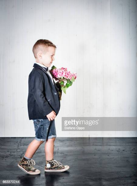 Kid in suit and bow tie with flowers