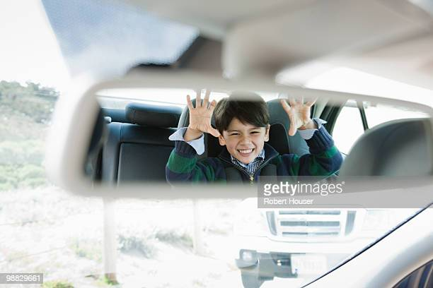 Kid in the back seat of a car.