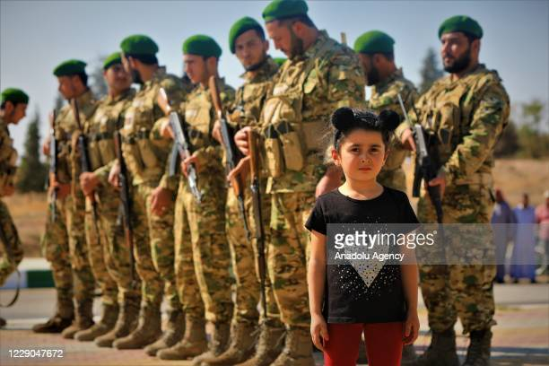 A kid is seen in front of the members of Syrian National Army as they attend an event to mark the first year of Operation Peace Spring as life turned...