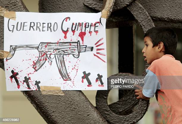 A kid is seen next to a sign reading Guerrero carries out during a protest of teachers in demand of justice for the deaths of six people including...