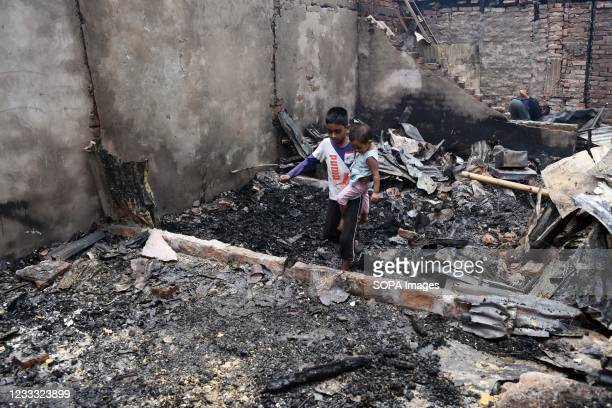 Kid is seen walking in a burned house after a fire swept through the slum. Several hundreds of houses were gutted as the devastating fire that broke...