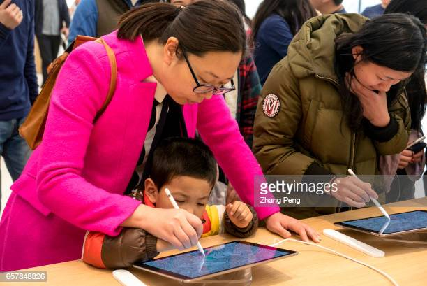 A kid is trying a painting application on iPad in the apple shop On the March 25 Apple opened 3 new retail shop in the world one of them is located...