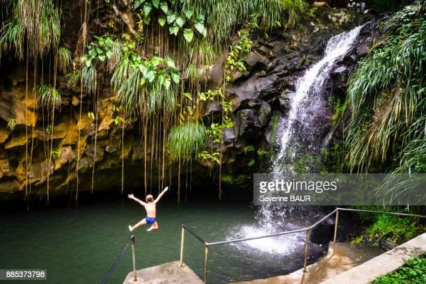 a kid jumping at the annandales falls, grenada, west indies - paisajes de isla de  granada fotografías e imágenes de stock