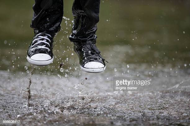 kid jumping in water - puddle stock pictures, royalty-free photos & images