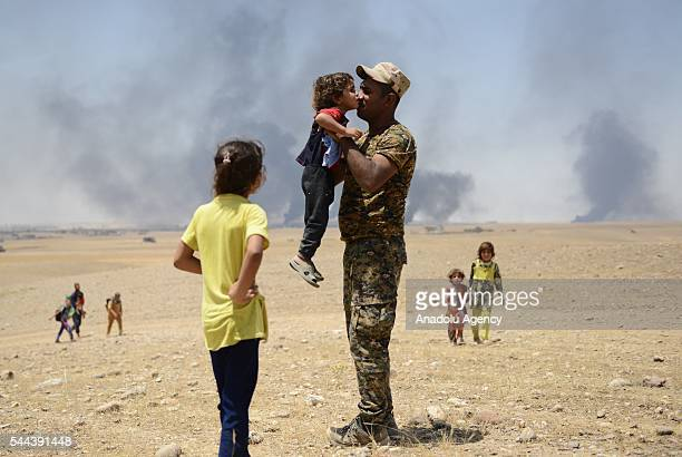A kid kisses an Iraqi soldier as they go to Dibege Tent Camp in Mosul's Mahmur district during Mosul rescue operation from Daesh in Mosul Iraq on...