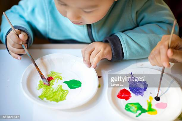 kid learning watercolor mixing - paper plate stock photos and pictures