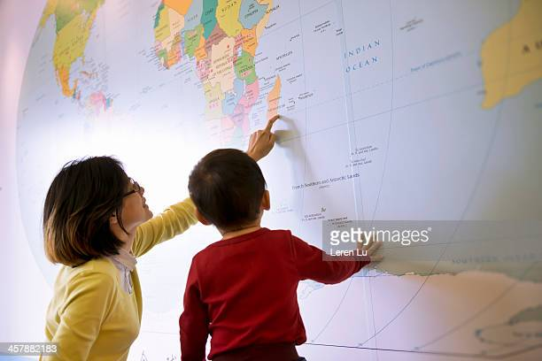 Kid learns about world map with mother