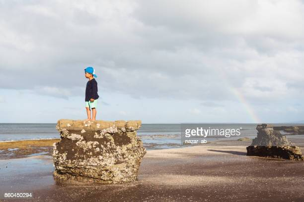 Kid looking towards coast with rainbow in background.