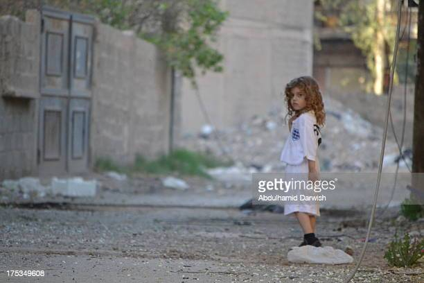 CONTENT] A kid looking towards the photographer in a bombed place in Deirezzor city east of Syria