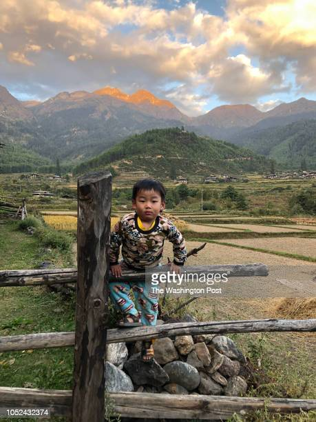 A kid looks on as Phub Tshering campaigns in the village of Chunje north of the town of Paro in Bhutan on October 14 2018
