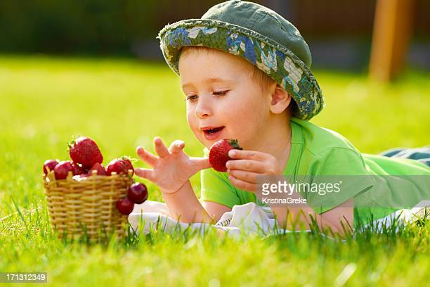 Kid lying down on the grass and eating strawberry