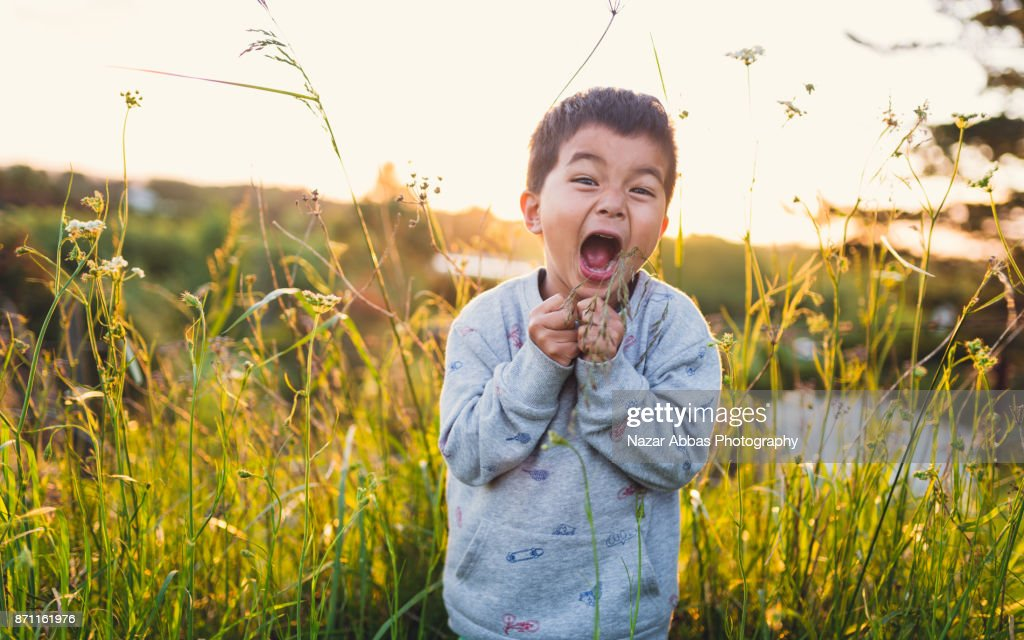 Kid making funny faces outdoor in lush meadow. : Stock Photo