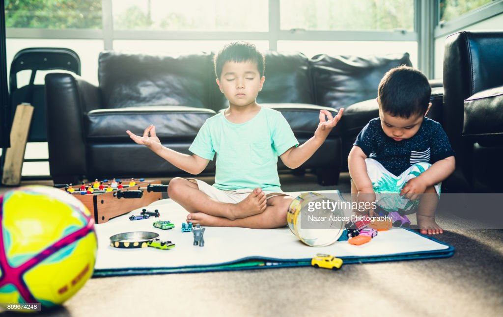 Kid meditation in messy room and playing with his brother. : Stock Photo