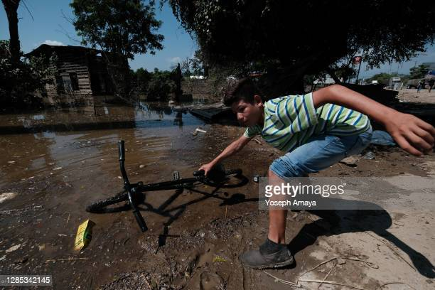 Kid of Colonia Planeta finds his lost bike in mud amid flooded streets after the flood produced by Tropical Storm Eta on November 11, 2020 in La...