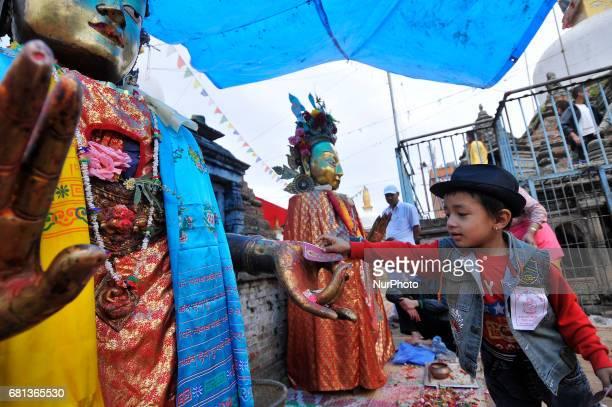 A kid offering ritual prayer towards Dipankar Buddha puts at the premises of Chiloncho Stupa during celebration the 2561 Buddha Purnima festival...