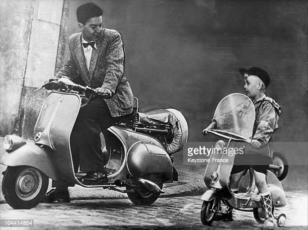 A kid on a toy vespa scooter beside to a young man on vespa scooter motorcycle in 1953