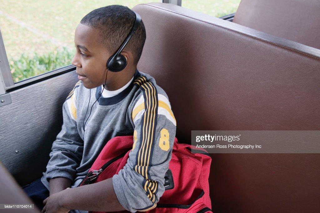Kid on School Bus Listening to Headphones : Stock Photo