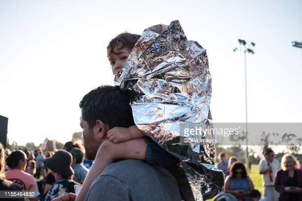 A kid on top of her parent's shoulders covered with foil paper during the protest Over one thousand people gathered in San Ysidro near the US Mexico...