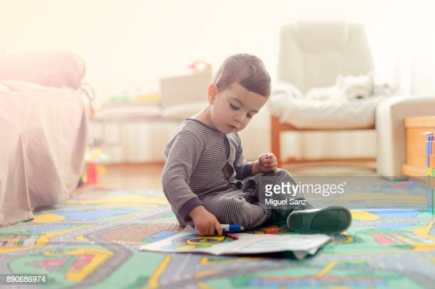 Kid painting a book at home