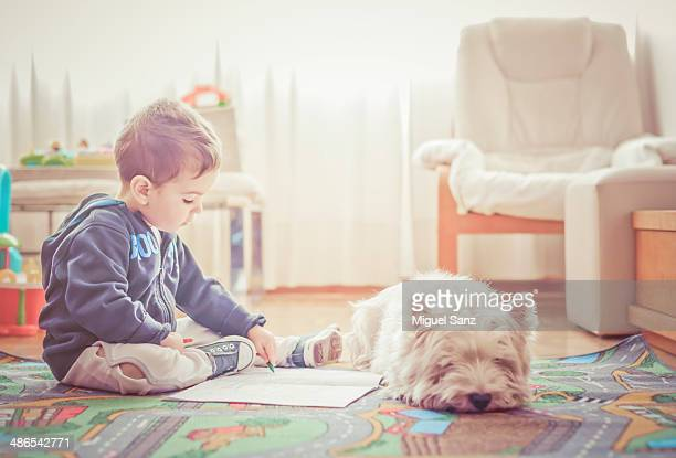 kid painting with his dog at home
