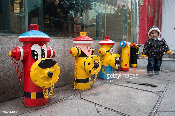 A kid passes by the fire hydrants painted as cartoon characters at Xinjiekou the central business district on January 13 2016 in Nanjing Jiangsu...