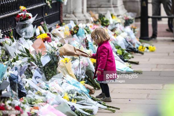 Kid paying tribute. Members of the public leave floral tributes for the late Prince Philip outside Buckingham Palace in London.