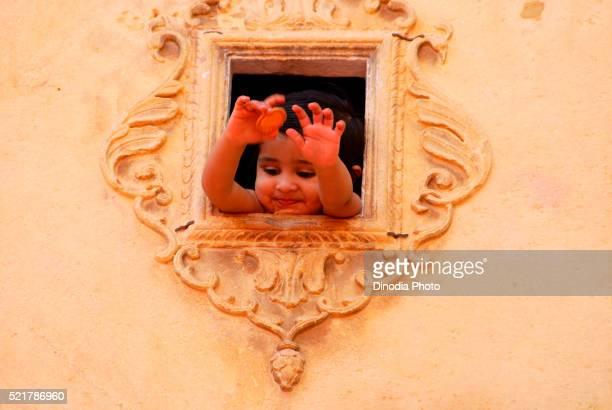 Kid peeping through window, Jodhpur, Rajasthan, India