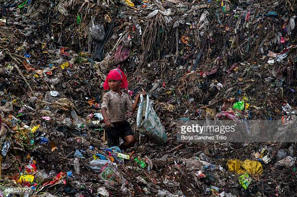A kid picks through trash in a landfill on November 17 2013 in Dhaka Bangladesh Bangladesh currently holds one of the lowest minimum wages in the...