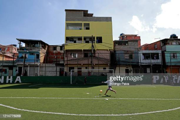 A kid play soccer during training to distribute donated food to residents of Paraisópolis favela on March 24 2020 in Sao Paulo Brazil Paraisopolis is...