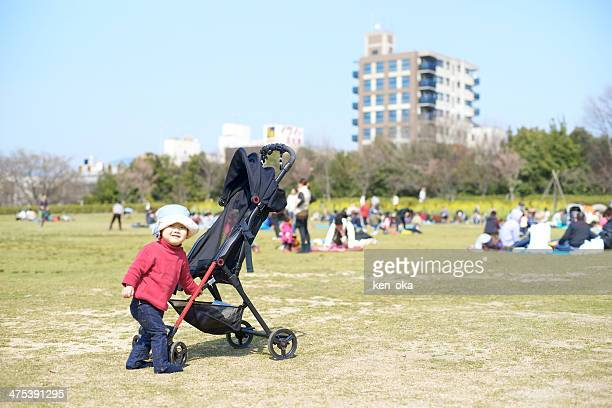 A kid play to push a buggy at spring park