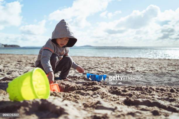 kid playing at beach in winter. - auckland stock pictures, royalty-free photos & images