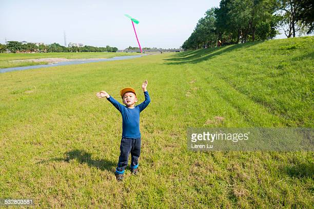kid playing bamboo dragonfly on grass - leren stock pictures, royalty-free photos & images