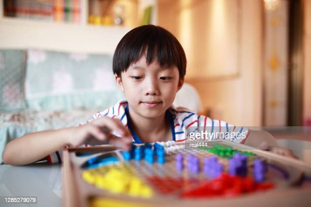 kid playing chinese checkers - chequers stock pictures, royalty-free photos & images