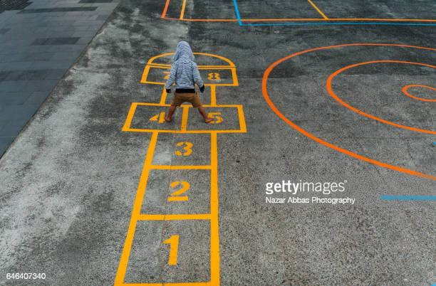 kid playing hopscotch in playground. - patio de colegio fotografías e imágenes de stock