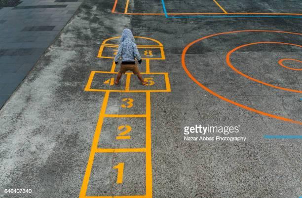 kid playing hopscotch in playground. - schulhof stock-fotos und bilder