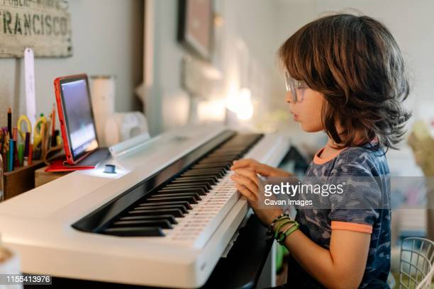 kid playing on a white smart piano keyword while look at  ipad - keyboard player stock pictures, royalty-free photos & images