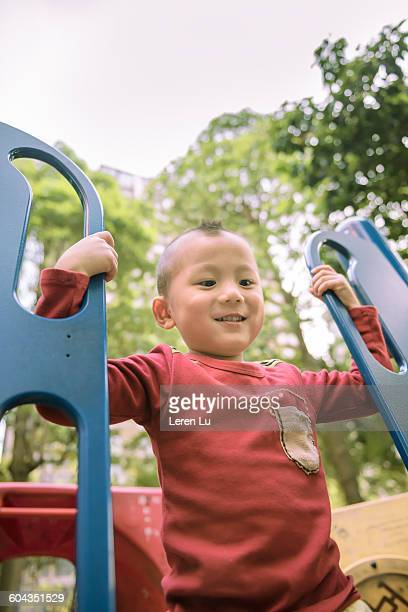 kid playing slide in playground - leren stock pictures, royalty-free photos & images