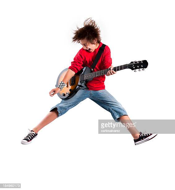 Kid playing the guitar while jumping in the air