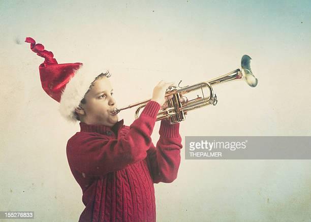 kid playing the trumpet wearing santa hat