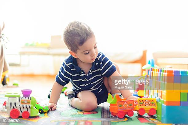 Kid playing with a train and small cars at home