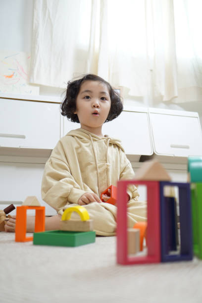 A Kid Playing with Toy Block