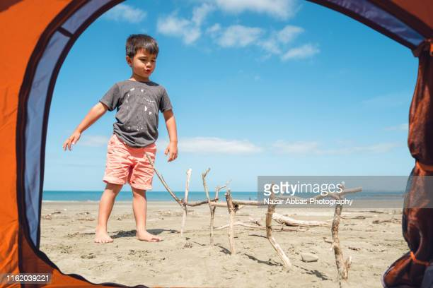 kid playing with wood at beach. - nazar abbas photography stock pictures, royalty-free photos & images