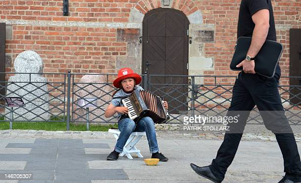A kid plays accordion for the visitors of the habour in Gdansk on June 12 2012 Poland and Ukraine cohost the 2012 European Football Championship AFP...