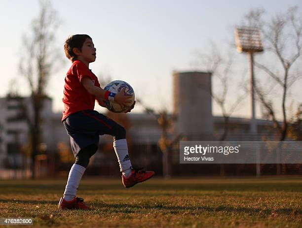 A kid plays football prior to the beginning of 2015 Copa America Chile close to National Stadium on June 08 2015 in Santiago Chile