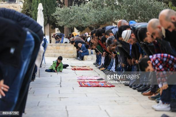A kid plays on the ground as Muslims perform the Friday Prayer alAqsa Mosque compound in Jerusalem on December 15 2017