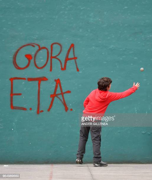 A kid plays 'pelota' next to a graffiti supporting Basque separatist group ETA in a 'fronton' of the Spanish Basque village of Hernani on May 5 2018