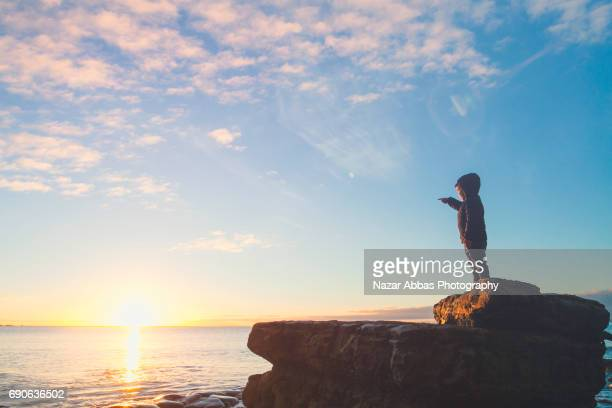 Kid Pointing to Sunrise While Standing On Rock.
