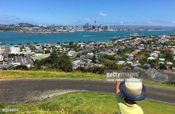 Kid pointing towards Auckland city.