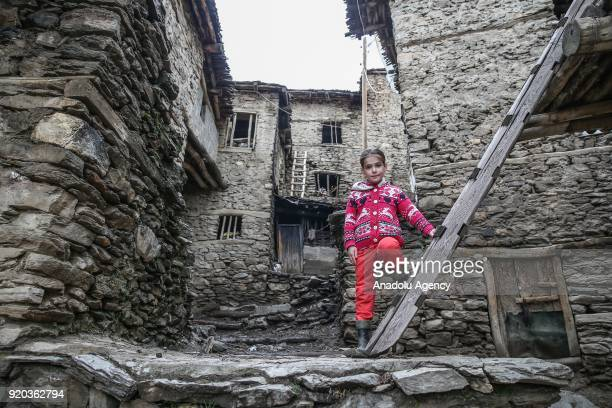 A kid poses for a photo in front of stone houses at her village at Hizan district in the southeastern province of Bitlis Turkey on February 18 2018...